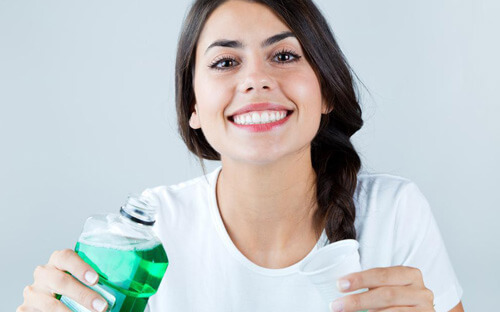Happy female smiling with a bottle of mouthwash