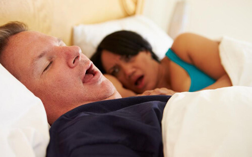 Male person snoring while female person is disturbed during sleep